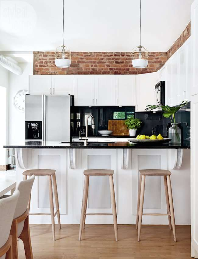 modern kitchen with brick walls above cabinets