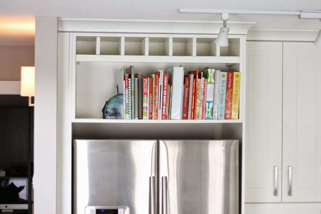 cookbooks in kitchen shelves above refrigerator