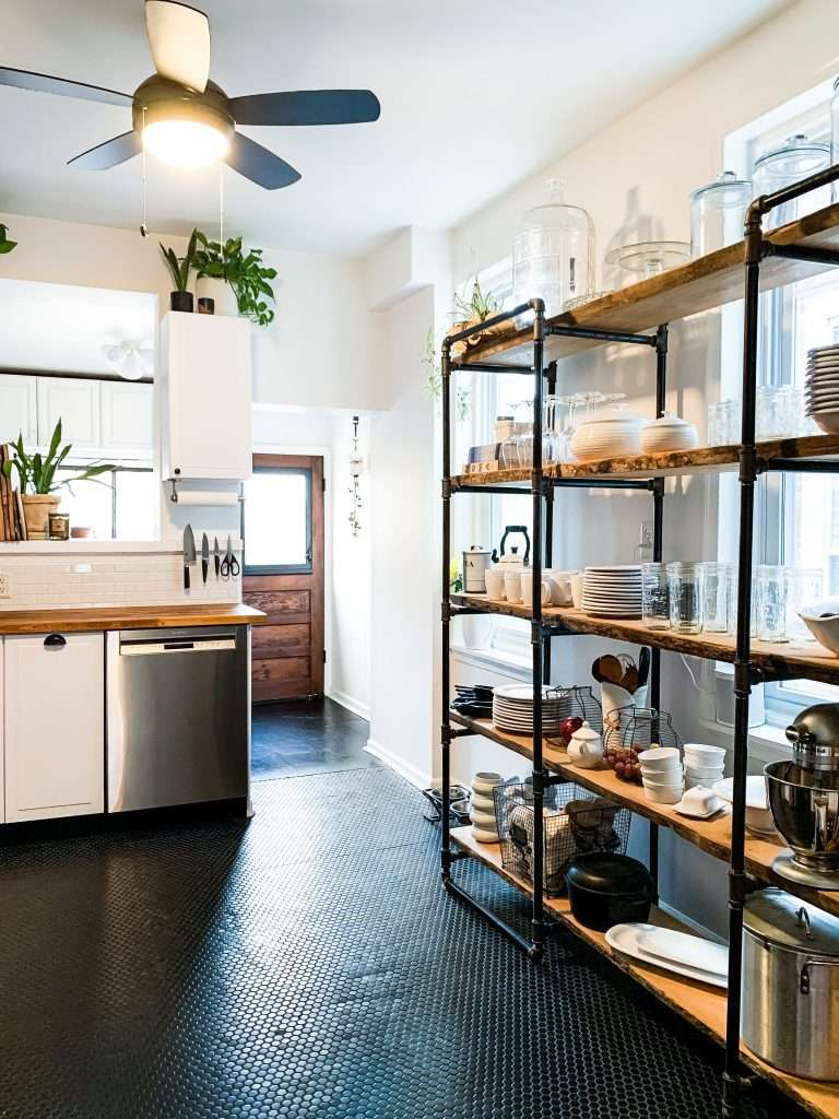 kitchen with black tile and wood industrial shelving unit