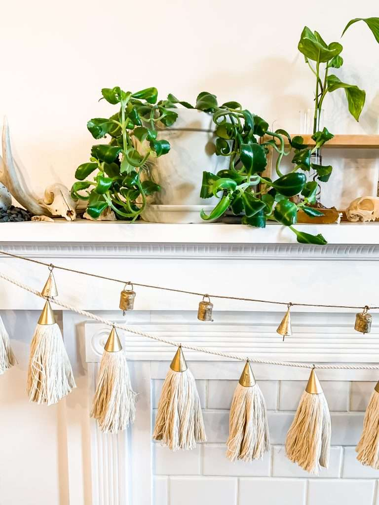 mantel with plants and bell and tassel garland