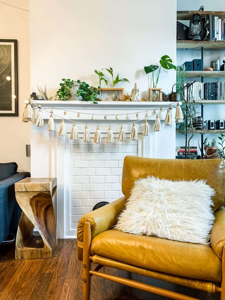 living room with bell and tassel garland on mantel and leather chair